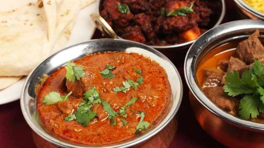 A-bowl-of-Kashmiri-lamb-curry-on-a-table-with-lamb-korma,-chicken-fry,-chappatis-and-rice-933896125
