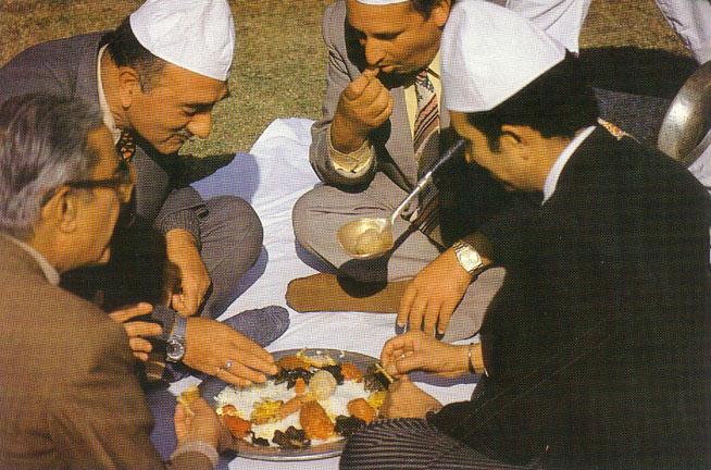 Four people having Wazwan in a Trammi