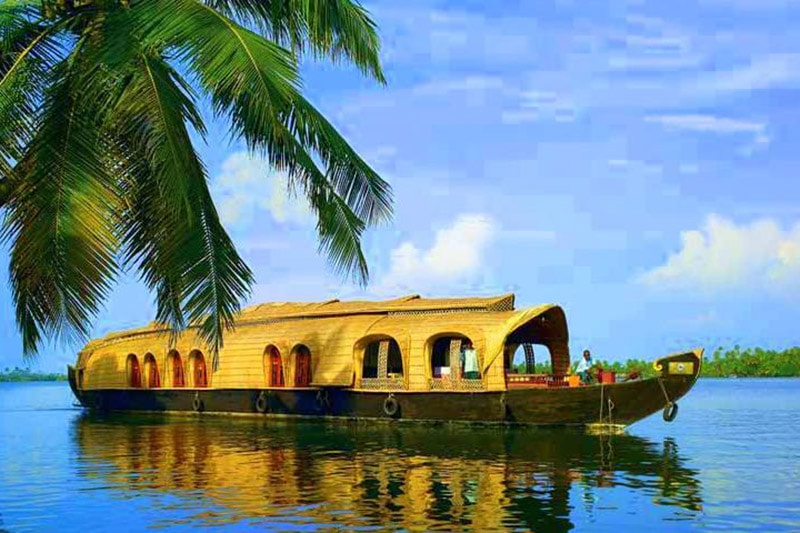 A houseboat in Alleppey traversing the deep blue backwaters